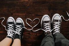 Les pieds aimant des espadrilles de couples tiennent le plancher en bois Photos libres de droits