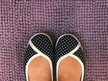 Les pieds asiatiques de femme portent des chaussures de sport de point de polka sur le tapis violet Photographie stock libre de droits