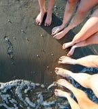 Les pieds aux pieds nus d'une famille de cinq avec de longues jambes sur l'arénacé soient Images libres de droits