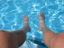Les pieds détendent dans l'eau de regroupement Image stock