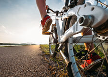 Les pieds d'enfant dans des espadrilles rouges commencent à monter une bicyclette Photo libre de droits