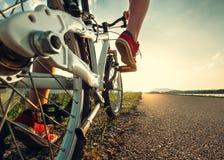 Les pieds d'enfant dans des espadrilles rouges commencent à monter une bicyclette Image libre de droits