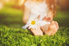 Les pieds d'enfant sur l'herbe verte en été se garent Photos stock