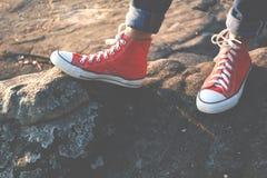 Les pieds d'espadrille rouge une fille en nature et détendent le temps Photo stock