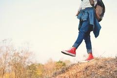 Les pieds d'espadrille rouge une fille en nature et détendent le temps Photos stock