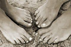 Les pieds d'un couple sur la plage dans le sable Photo libre de droits