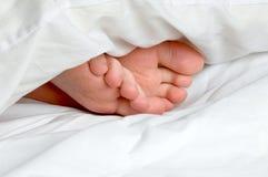 Les pieds d'un enfant de sommeil dans la literie Photo libre de droits