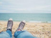 Les pieds d'un jeune homme sur la plage Image libre de droits