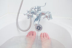 Les pieds d'une jeune femme dans une baignoire photo stock