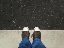 Les pieds dans des chaussures de toile se tenant sur l'asphalte ont aligné avec marquage routier Photos libres de droits