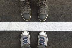 Les pieds dans des espadrilles, tanding à côté de la rue blanche raye Photos stock