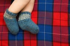 Les pieds de bébé nouveau-né dans un bleu ont tricoté les chaussettes de laine sur le backgrou Image libre de droits