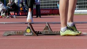 Les pieds de coureur de fille se tient à côté des blocs commençants avant début banque de vidéos