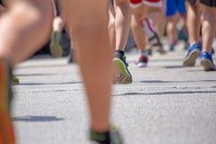 Les pieds de coureur soutiennent la course sur l'action d'asphalte Image stock