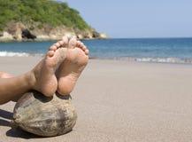 Les pieds de femme reposant la noix de coco échouent, le Costa Rica Images stock