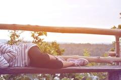 Les pieds de fille et espadrilles sur le fond de ciel bleu dans les vacances, détendent t Images stock