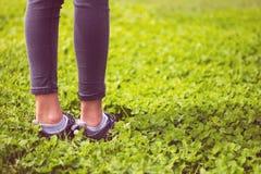 Les pieds de jeune fille dans le sport chausse des espadrilles sur l'herbe verte sur le pré Image libre de droits