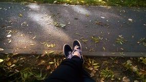 Les pieds de jeunes filles sur la traînée en parc Photos stock