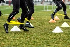 Les pieds de joueurs de PAOK et de matériel de formation du football Image stock