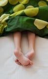 Les pieds de l'enfant sous la couverture Images libres de droits