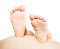 Les pieds de l'enfant sur le ventre enceinte images libres de droits