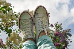 Les pieds de la femme dans des espadrilles blanches contre la fleur lilas et le ciel bleu Image stock