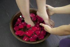 Les pieds de la femme imbibant dans l'eau de Rose Petals Images stock