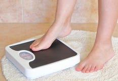 Les pieds de la femme sur l'échelle de salle de bains Images libres de droits