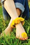 Les pieds de la jeune femme sur l'herbe ont orné avec des pissenlits images libres de droits