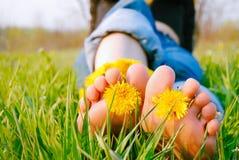 Les pieds de la jeune femme sur l'herbe ont orné avec des pissenlits photos libres de droits