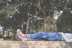 Les pieds de la jeune fille dorment en parc Image stock