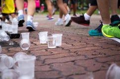 Les pieds de marathoniens et les tasses emptry de l'eau sur le rafraîchissement se dirigent Photographie stock libre de droits