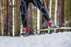 Les pieds de skieur d'hommes pulvérise la neige de dessous le ski Images stock
