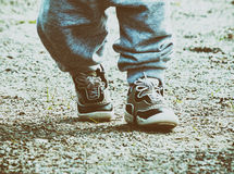 Les pieds des enfants dans le pantalon et des espadrilles de sports Images libres de droits