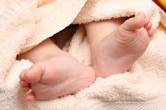 Les pieds des enfants dans les mains de la mère Image stock