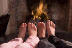 Les pieds des enfants réchauffant à une cheminée Photos stock