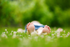 Les pieds des enfants sur l'herbe dehors Images stock