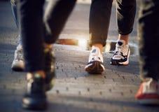 Les pieds des femmes dans des chaussures de sports parmi la foule des passants image libre de droits
