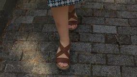 Les pieds des femmes en sandales sont sur la route banque de vidéos