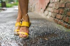 Les pieds des femmes sous les baisses de pluie Photographie stock libre de droits