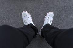 Les pieds des hommes dans les pantalons noirs et des espadrilles blanches Photographie stock libre de droits