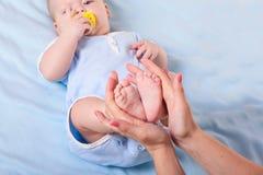Les pieds du bébé dans des mains de la mère Photo libre de droits