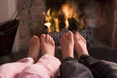 Les pieds du couple réchauffant à une cheminée images libres de droits