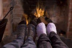 Les pieds du couple réchauffant à une cheminée photographie stock