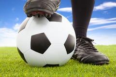 Les pieds du footballeur dans la pose occasionnelle sur un terrain de jeu ouvert Photos stock