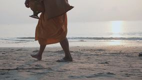 Les pieds du moine bouddhiste marche sur la plage avec l'urne dans des mains au matin clips vidéos