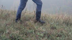 Les pieds du ` s d'homme monte sur l'herbe humide en brouillard, fin, MOIS lent banque de vidéos