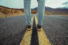 Les pieds du ` s d'hommes se tenant sur l'asphalte abandonnent la route avec les lignes jaunes d'inscription Espadrilles et jeans Photo stock