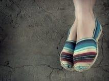 Les pieds du ` s de femme avec la toile portée chausse le repos contre un plancher cimenté Photos libres de droits