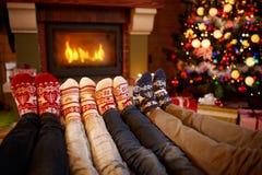Les pieds en laine cogne près de la cheminée dans le temps de Noël Images stock